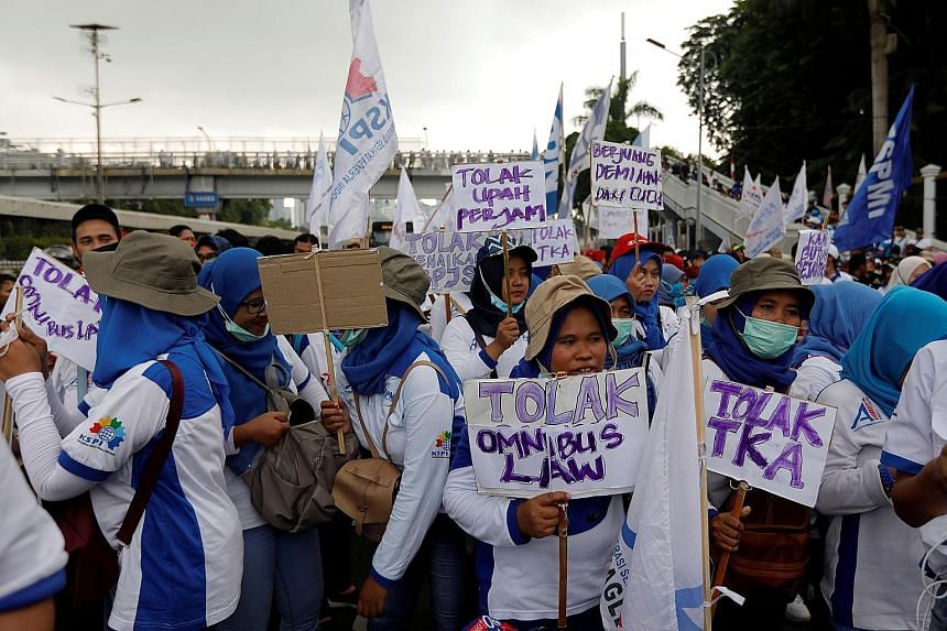 """Labourers carrying placards which say """"Against omnibus law and foreign workers"""" during a protest outside Parliament building in the Indonesian capital Jakarta yesterday. According to a union leader, the reforms could increase the risk of mass firings"""