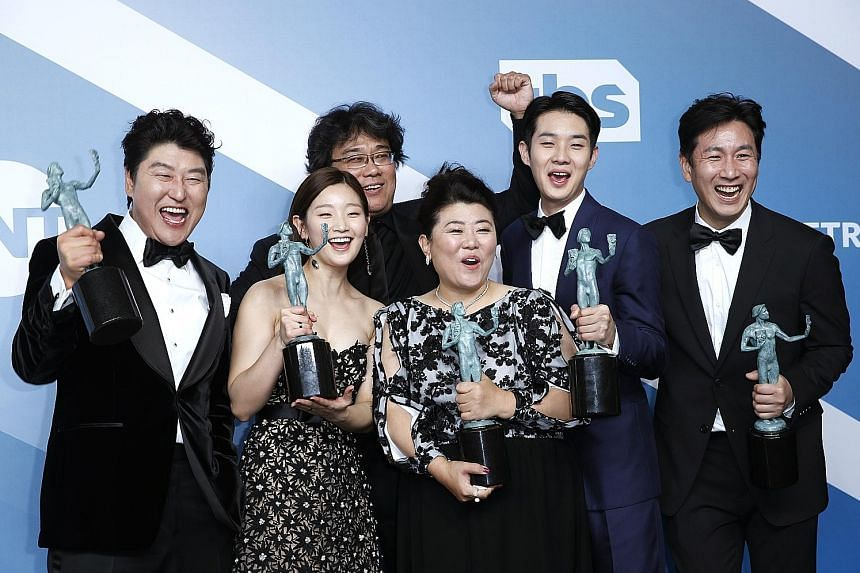 Director Bong Joon-ho (third from left) with the cast of Parasite (from left) Song Kang-ho, Park So-dam, Lee Jeong-eun, Choi Woo-shik and Lee Sun-kyun, who took the top prize of best movie ensemble cast. Jennifer Aniston (top) won the best actress in