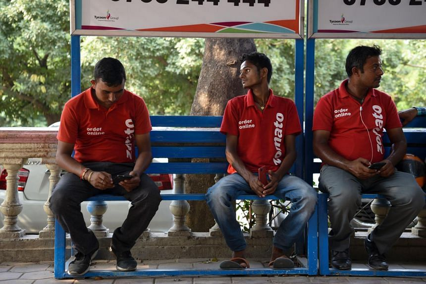 Zomato delivery workers waiting to receive orders in Gurugram, India.