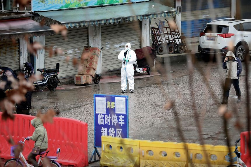 A worker in a protective suit is seen at the closed seafood market in Wuhan, Hubei province, on Jan 10, 2020.
