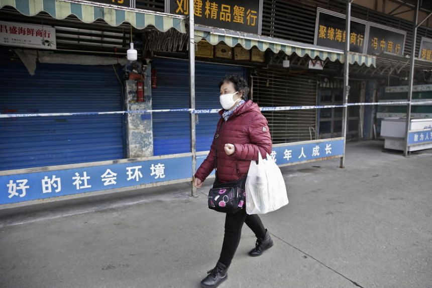 A woman wears a mask while walking past the closed Huanan Seafood Wholesale Market, which has been linked to cases of a new strain of coronavirus identified as the cause of the pneumonia outbreak in Wuhan, China, on Jan 20, 2020.