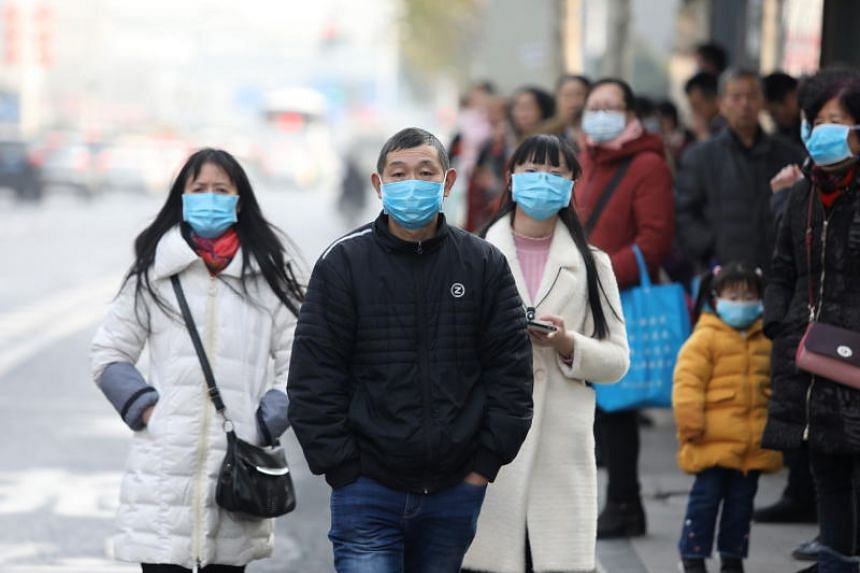 Chinese residents wear masks while waiting at a bus stop in Wuhan, China, on Jan 20, 2020.