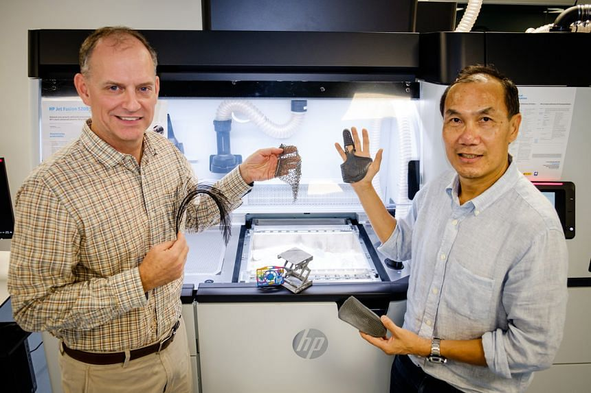 NTU Professor Tan Ming Jen and Dr Mike Regan, co-directors of the HP-NTU Corporate Lab, holding up 3D-printed products from the HP Multi Jet Fusion 3D printer.