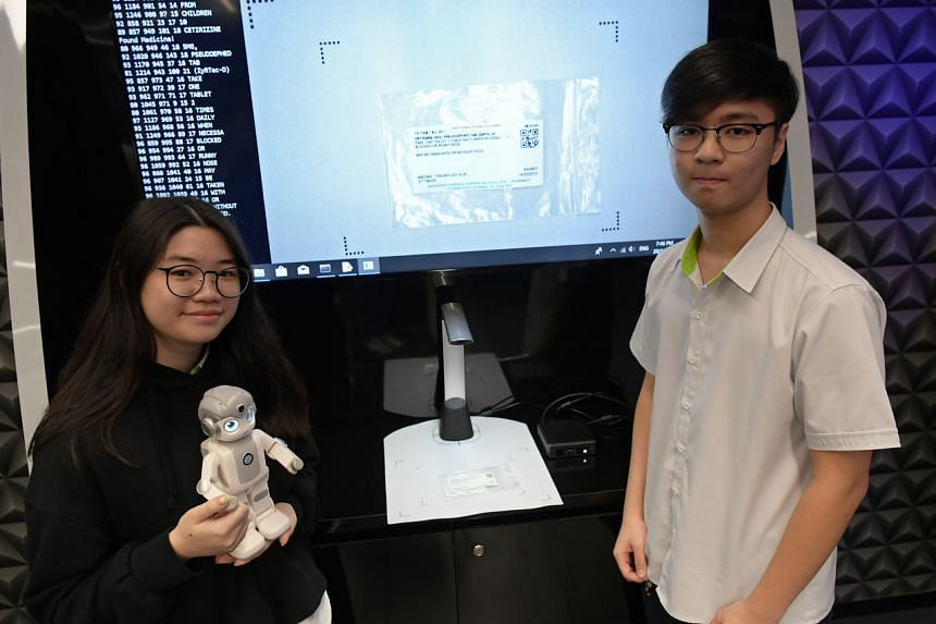 Institute of Technical Education students Chew Chu Xuan and Glenda Chong developed a mini-robot that reminds elderly patients to take their medication.