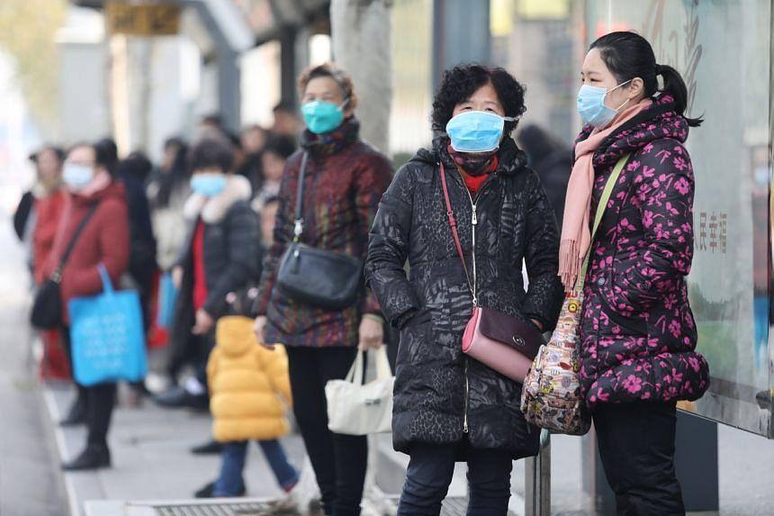 Residents wearing masks while waiting at a bus station near the closed Huanan Seafood Wholesale Market on Jan 20, 2020.