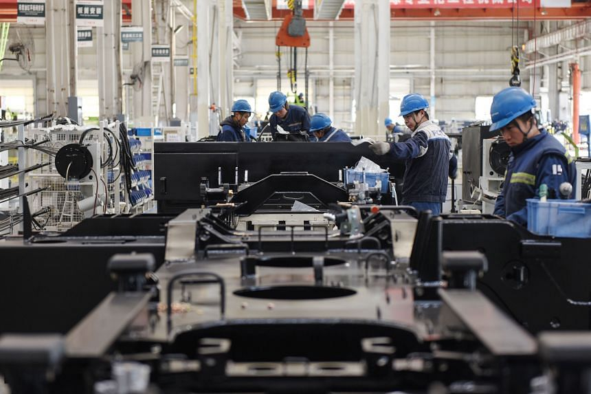 An employee works on a crane production line at a factory in Zhangjiakou in China's northern Hebei province, on Jan 13, 2020.
