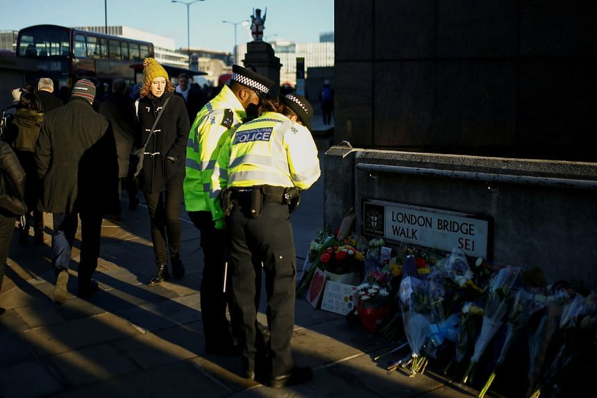 In a photo from Dec 2, 2019, police officers look at flowers and signs left at the scene of a fatal attack on London Bridge in London.