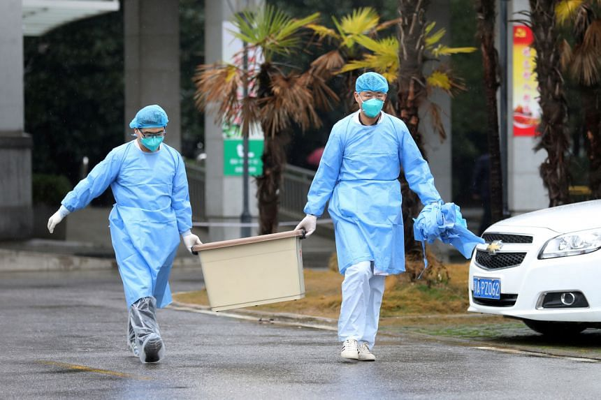 Medical staff carry a box as they walk at the Jinyintan hospital, where the patients with pneumonia caused by the new strain of coronavirus are being treated, in Wuhan, Hubei province, on Jan 10, 2020.