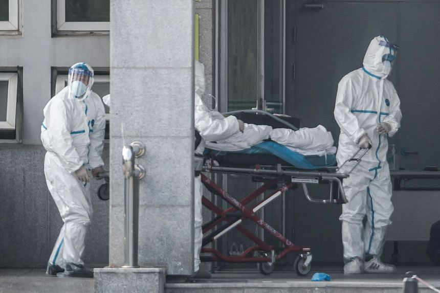 Medical staff members carry a patient into the Jinyintan hospital, where patients infected by a mysterious SARS-like virus are being treated, in Wuhan in China's central Hubei province on Jan 18, 2020.