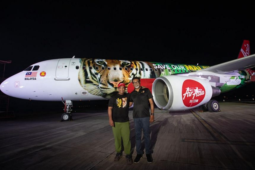 """AirAsia chief Tony Fernandes (left) and Malaysian Water, Land and Natural Resources Minister Xavier Jayakumar in front of one of the airline's planes sporting a """"Save Our Malayan Tiger"""" livery."""