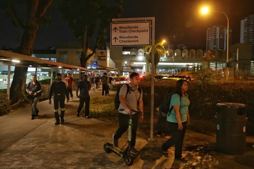 A man pushes his e-scooter on the footpath upon exiting the Woodlands Train Checkpoint on Jan 15, 2020.