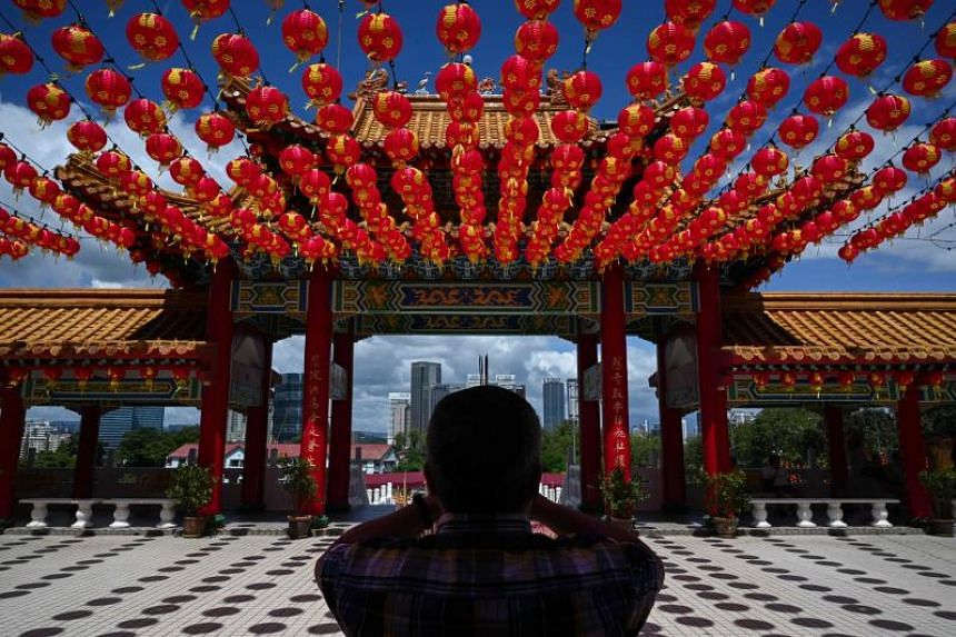 A man prays under traditional Chinese lanterns decoration at the Thean Hou temple ahead of the Lunar New Year celebrations in Kuala Lumpur on Jan 9, 2020.