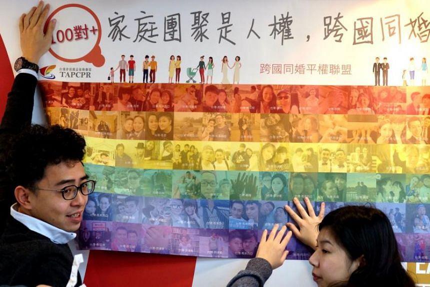 Activists from the Taiwan Alliance to Promote Civil Partnership Rights unfurl a poster in support of same-sex marriage in Taipei, on Jan 21, 2020.
