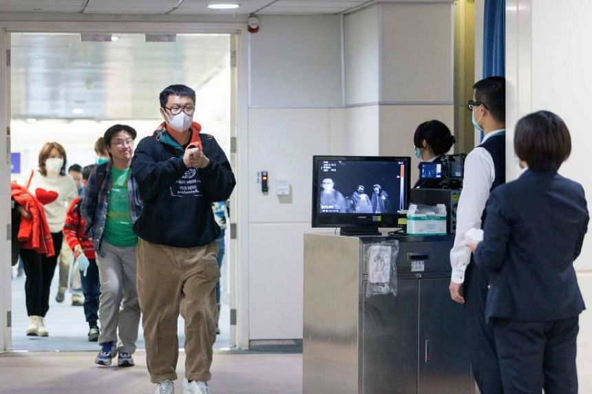 A photo taken on Jan 13, 2020, shows Taiwan's Centres for Disease Control personnel using thermal scanners to screen passengers arriving on a flight from China's Wuhan province at the Taoyuan International Airport.