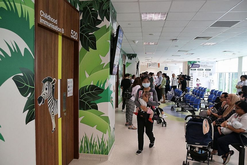 Parents queueing to have their children immunised at the Temasek Foundation Integrated Maternal and Child Wellness Hub yesterday. Minister for Manpower and Second Minister for Home Affairs Josephine Teo applauding as Madam Radina Roslan and her 21-mo