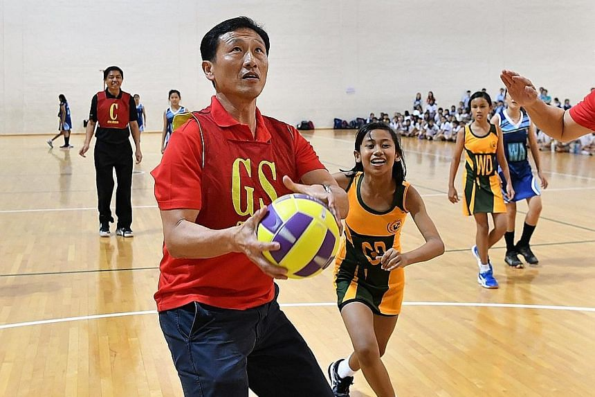 Education Minister Ong Ye Kung poised to shoot the ball in a netball game at the opening ceremony of National School Games yesterday. ST PHOTO: CHONG JUN LIANG