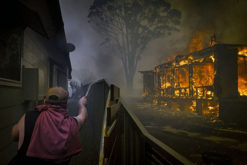 A man trying to protect his property from fires in Lake Conjola, New South Wales, Australia, on Dec 31, 2019.