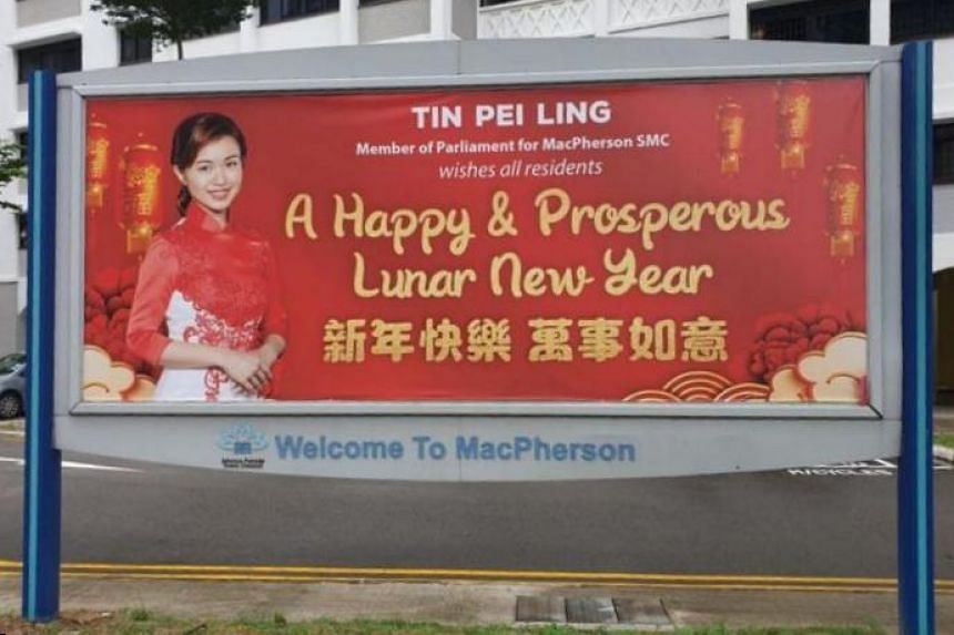 "The original banner (above) bears a greeting by Ms Tin, wishing residents ""a happy and prosperous Lunar New Year"" in English and Chinese, alongside a photo of her in a red and white outfit."
