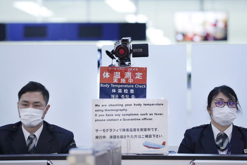 Officers work at a health screening station as they observe passengers arriving on a flight from Wuhan where a SARS-like virus was discovered and has since spread at Narita airport on Jan 16, 2020,