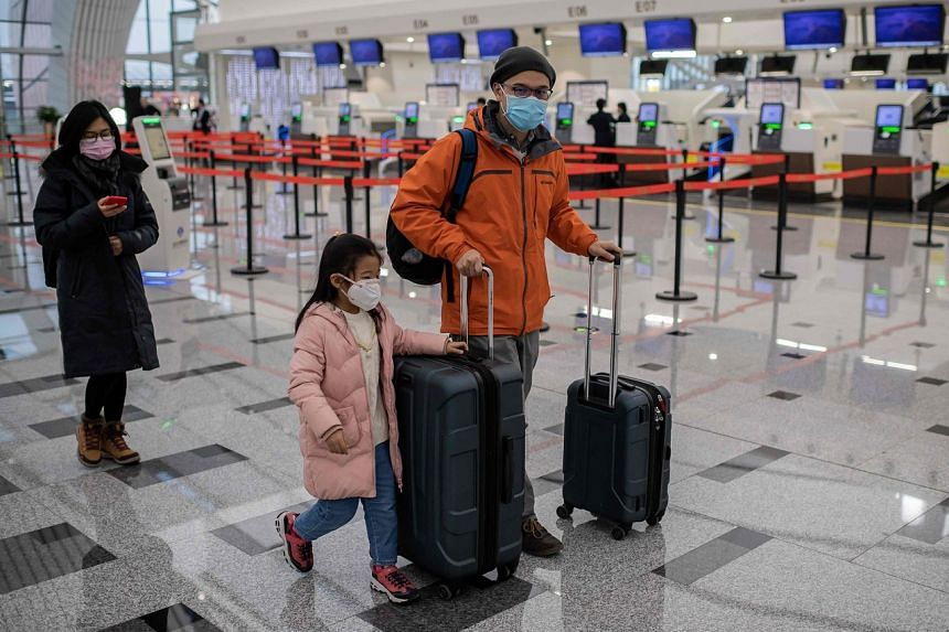 Travellers wear protective masks at the check-in area of the Daxing International Airport in Beijing, on Jan 21, 2020.