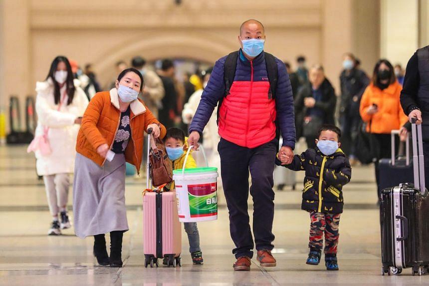 Commuters wearing face masks walk in Hankou railway station in Wuhan on Jan 21, 2020.