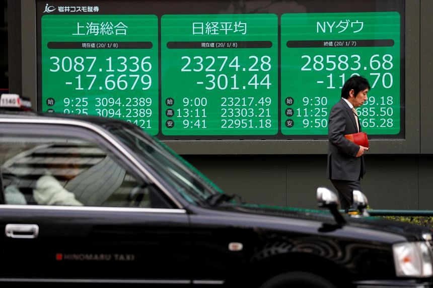A man walks past an electronic display showing Asian markets indices outside a brokerage in Tokyo on Jan 8, 2020.