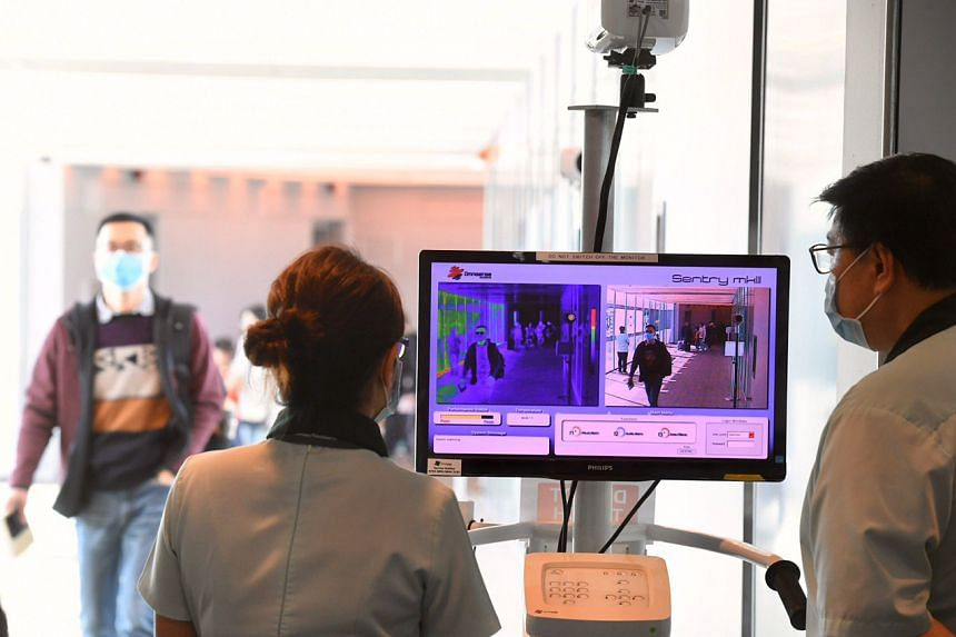 Passengers arriving at Changi Airport Terminal 3 from a Hangzhou flight going through a thermal scanner on Jan 22, 2020.