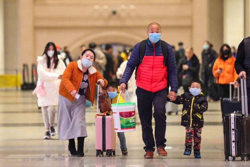 Passengers wearing protective masks walk inside Hankou Railway Station in Wuhan, Jan 21, 2020.