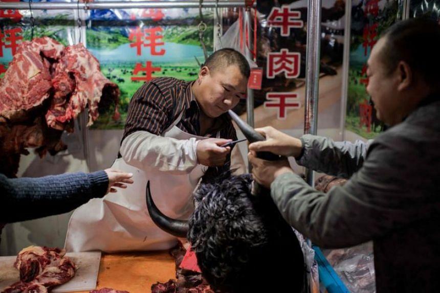 A photo taken on Jan 15, 2020, showing a butcher selling yak meat at a market in Beijing.