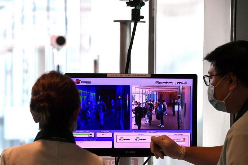 Passengers arriving at Changi Airport Terminal 3 from a Hangzhou flight go through a thermal scanner on Jan 22, 2020.