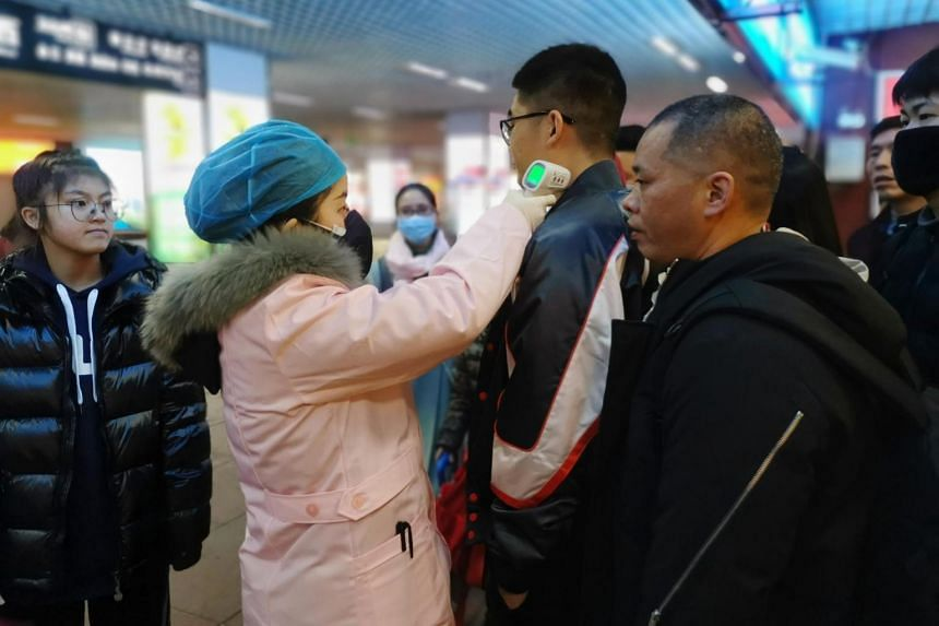 A staff member checks the body temperature of passengers as they arrive at a railway station in Yingtan City, Jiangxi province, China, on Jan 22, 2020.