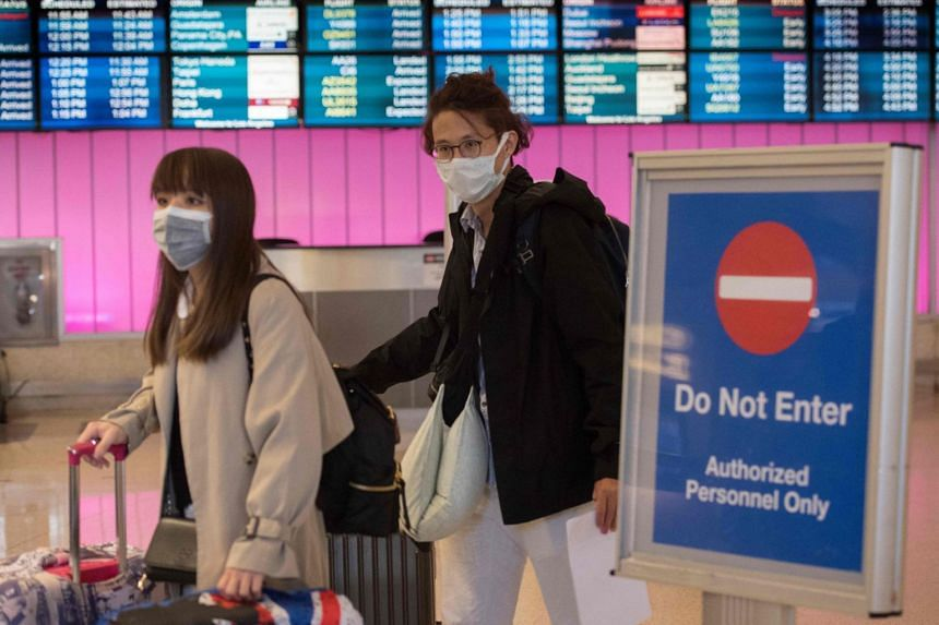 Passengers wear protective masks at the Los Angeles International Airport, California, on Jan 22, 2020. The coronavirus has killed 17 people and infected more than 600, most in China but cases have been detected as far away as the United States.