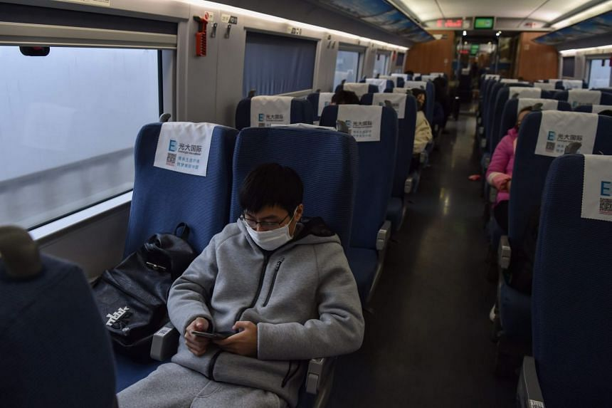 A young man wearing a protective facemask sits on a train as he travels from the Chinese city of Shanghai to his hometown of Wuhan, on Jan 23, 2020.