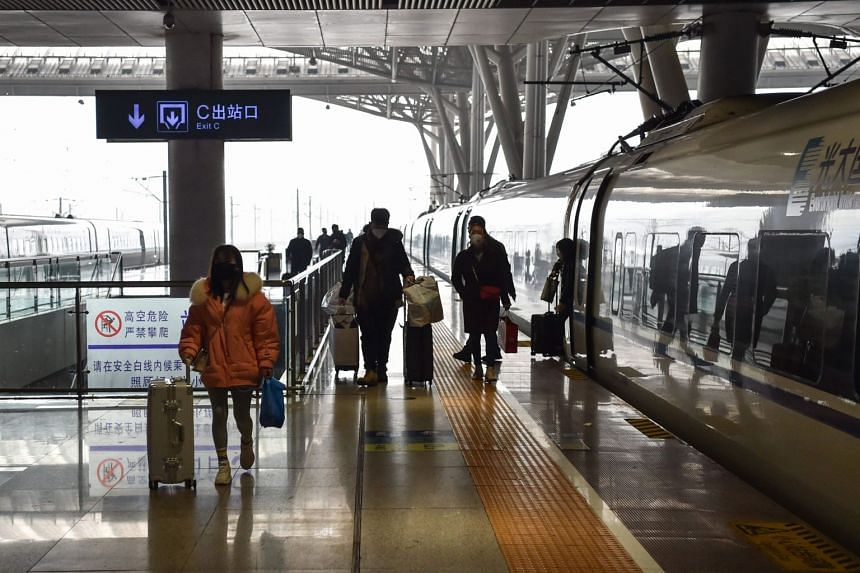 Travellers arrive at the nearly-deserted Wuhan train station in Wuhan, on Jan 23, 2020.