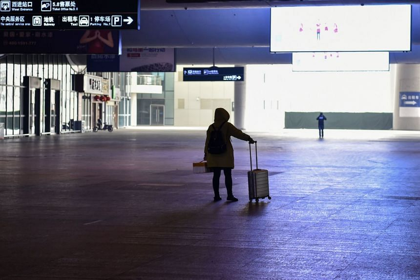 A passenger stands after arriving at the nearly-deserted Wuhan train station in Wuhan, on Jan 23, 2020.