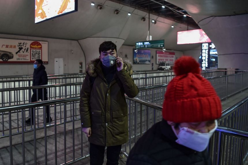 People wait for taxis after arriving at the nearly-deserted Wuhan train station in Wuhan, on Jan 23, 2020.