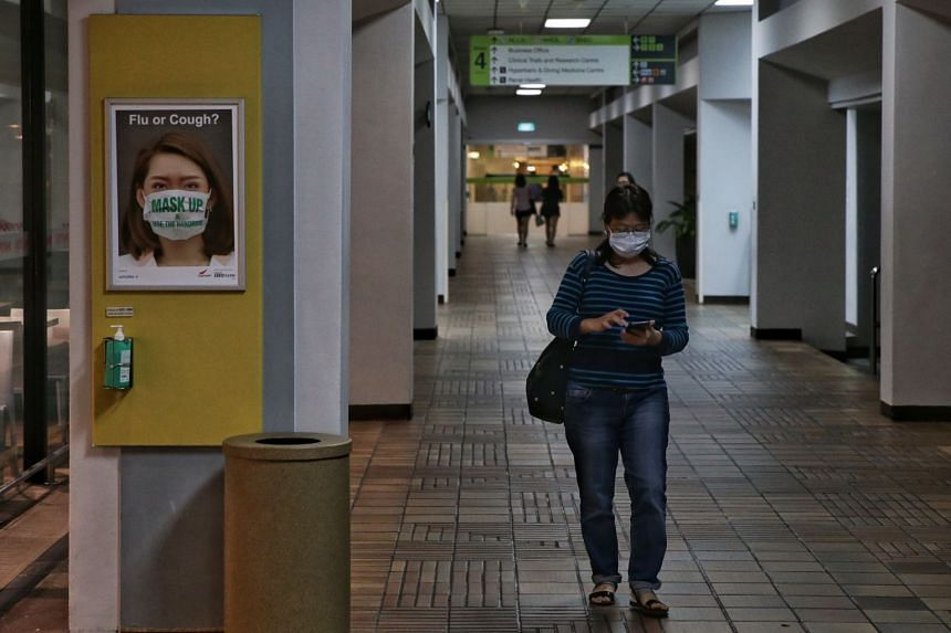 A woman wearing a face mask walks past a poster in Singapore General Hospital on Jan 23, 2020.