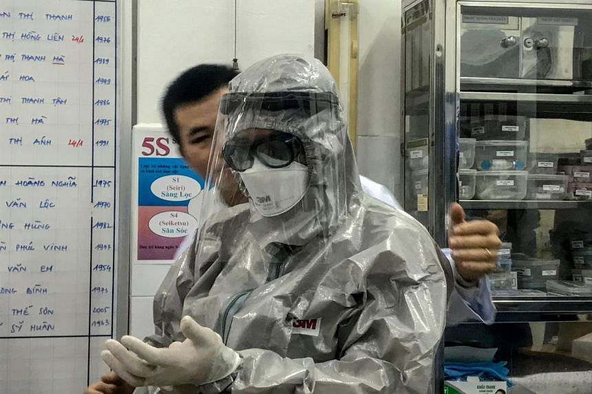 Vietnam's Deputy Minister of Health Nguyen Truong Son putting on a protective suit before entering an isolation area to visit the first two cases of the new coronavirus infection in Cho Ray hospital in Ho Chi Minh City on Jan 23, 2020.
