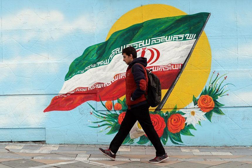 An Iranian boy walks past a wall painting of Iran's national flag in Teheran.