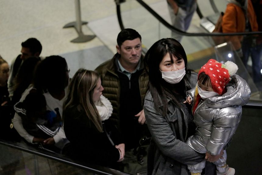Travellers wearing masks arrive on a direct flight from China at Seattle-Tacoma International Airport in SeaTac, Washington.
