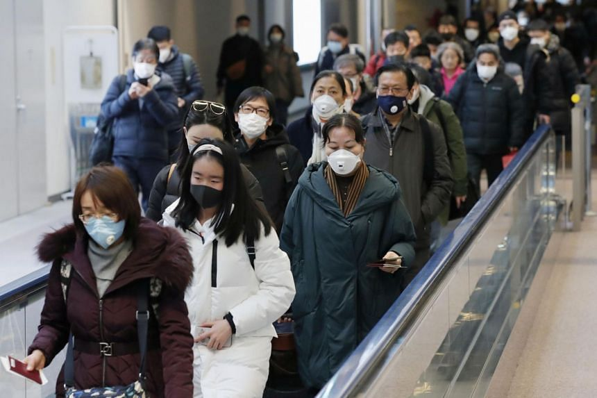 Passengers arriving from the Chinese city of Wuhan arrive at Narita Airport in Chiba, Japan, Jan 23, 2020.