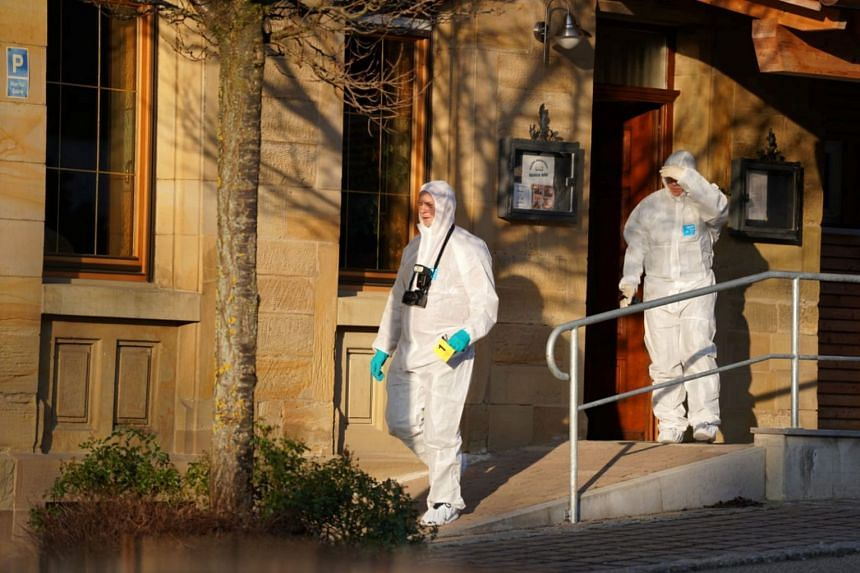 Forensic experts leave the scene of the shooting.