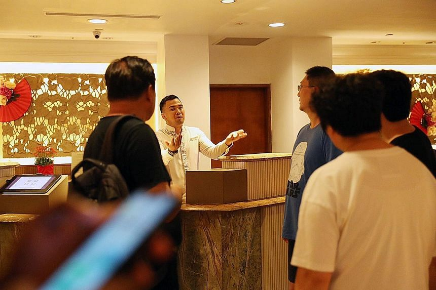 Mr Kelvin Yu (in blue T-shirt), who was staying at Shangri-La's Rasa Sentosa Resort & Spa with his family, asking a hotel employee yesterday which room the infected guest had stayed in. ST PHOTO: TIMOTHY DAVID
