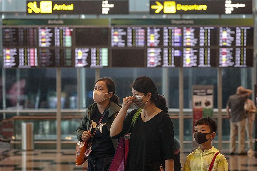 A family donning masks at Changi Airport yesterday. There is widespread concern that travel in and out of China during the upcoming Chinese New Year holiday could allow the mystery Wuhan virus to spread even further and faster.