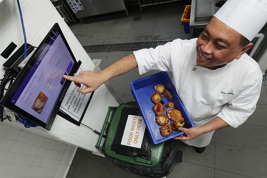 Shangri-La Hotel Singapore's kitchen division trainer Mohd Amer Hashim demonstrating how the hotel tackles food wastage using the Winnow system, which weighs and tracks food items left over at buffets and catered meals, and provides data to guide che