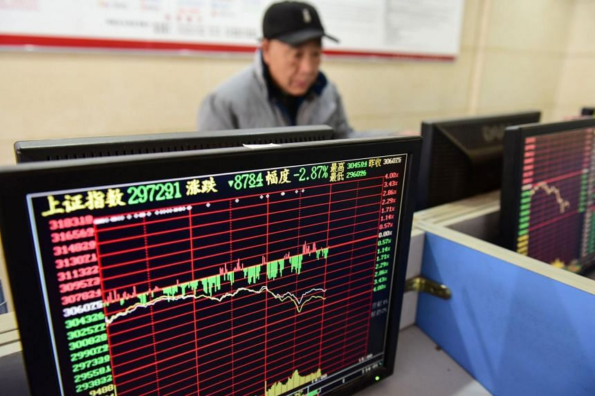 An investor looks at a screen showing stock market movements at a securities company in Fuyang in China's eastern Anhui province on Jan 23, 2020.
