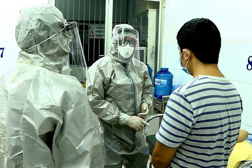 Medical personnel wearing protective suits interact with two patients (right, on bed, and standing) tested positive for the coronavirus in an isolation room at Cho Ray hospital in Ho Chi Minh City on Jan 23, 2020.