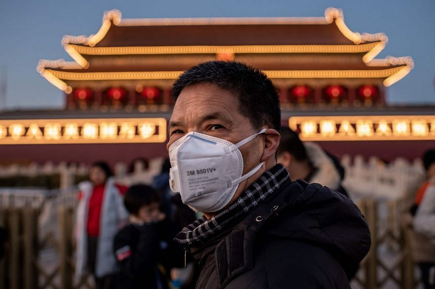 A man wearing a protective mask looks on as he walks past Tiananmen Gate in Beijing.