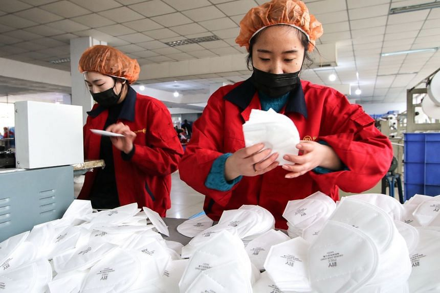Workers produce face masks at a factory in Handan, in China's northern Hebei province.