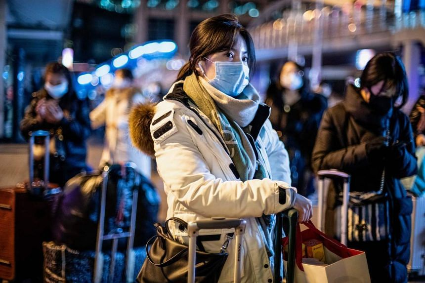 A woman wearing a protective mask looks on as she arrives at Beijing railway station ahead of the Lunar New Year in Beijing on Jan 23, 2020.